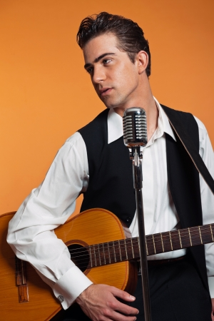 Retro country singer with guitar wearing black suit. Studio shot. photo