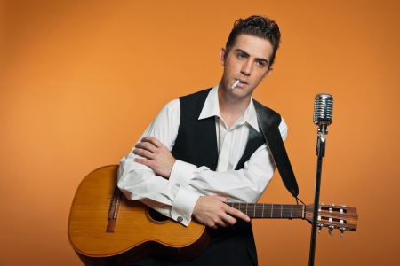 Retro country singer with guitar wearing black suit. Smoking cigarette. Studio shot. photo