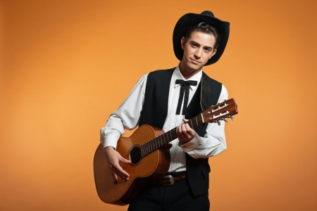 Retro country male guitar player wearing black suit and hat. Studio shot.