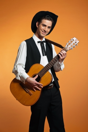 Retro country male guitar player wearing black suit and hat. Studio shot. photo
