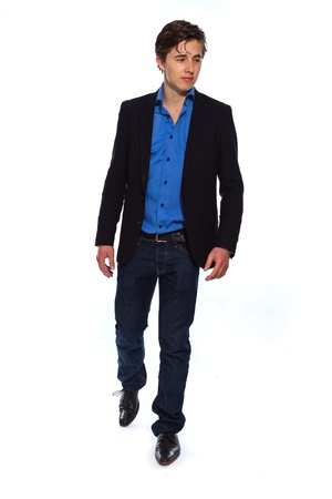 Walking young business man wearing blue jacket and jeans. Isolated on white. photo