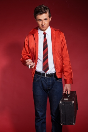 Retro fifties fashion man wearing red jacket and jeans. Holding a case and smoking. photo