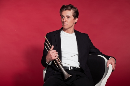 Retro fifties trumpet player wearing black suit. Sitting in chair. Red background. photo