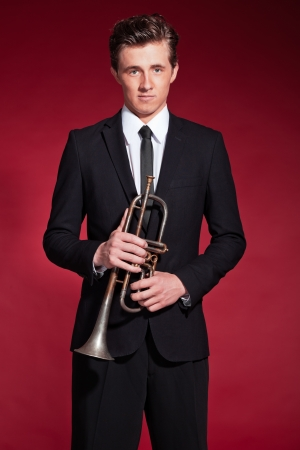 Retro fifties trumpet player wearing black suit. Holding his trumpet. Red background. photo