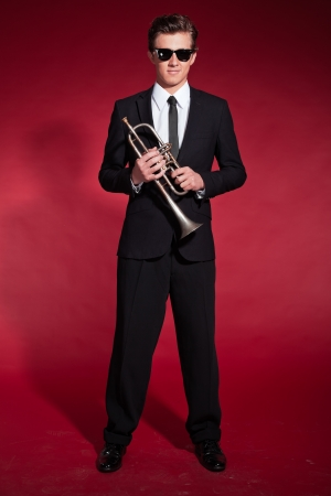 Retro fifties trumpet player wearing black suit and sunglasses. Holding trumpet. Red wall. photo