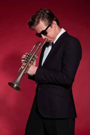 Retro fifties trumpet player wearing black suit and sunglasses. Blowing trumpet. Red wall. photo