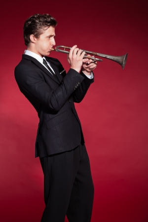 Retro fifties trumpet player wearing black suit. Playing trumpet. Red wall. photo