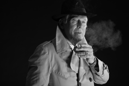 Retro mafia man with hat smoking cigarette. Black and white photo. photo
