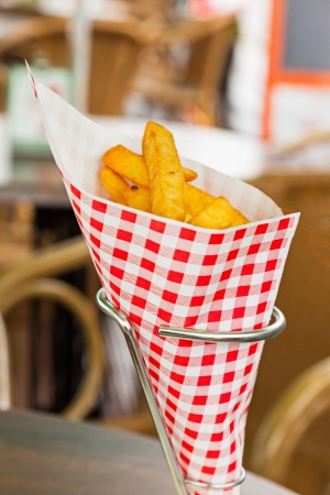 French fries in red and white blocked paper bag on table outdoor. photo