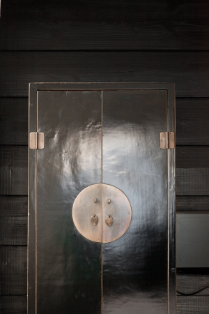 Black japanese style wardrobe standing against black wooden wall  photo