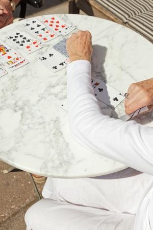 Senior woman playing card game outdoor in garden. photo