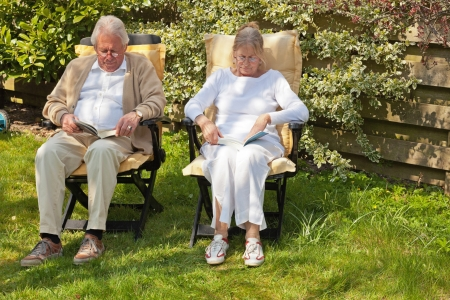 Senior couple sitting in garden reading a book. Summer time. photo