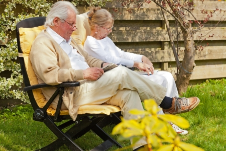 Senior couple sitting in garden reading a book photo