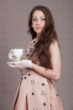 Retro romantic fashion woman with long hair in pink dress. Holding white tea cup. photo