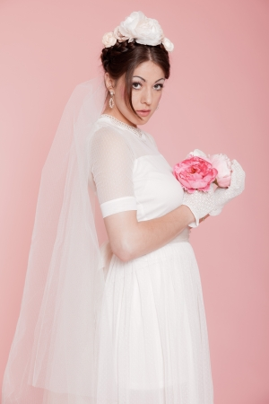 Retro romantic bride in white wedding dress. Decorated with flowers. Pink background. photo