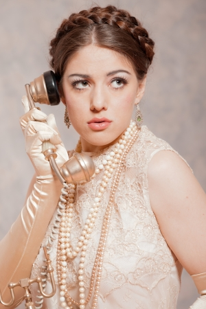 Retro romantic empire fashion woman. Calling with old telephone. Marble wallpaper. photo