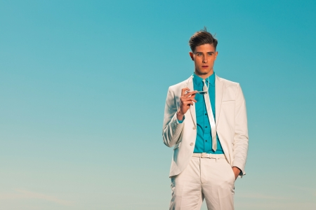 Retro summer 50s fashion man with white suit. Holding sunglasses Stock Photo - 19879532