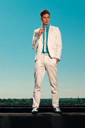 Retro summer 50s fashion man with white suit. Holding sunglasses Stock Photo - 19879565