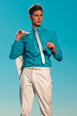 50 homem de moda ver�o do vintage com terno branco, segurando casaco e �culos de sol Banco de Imagens