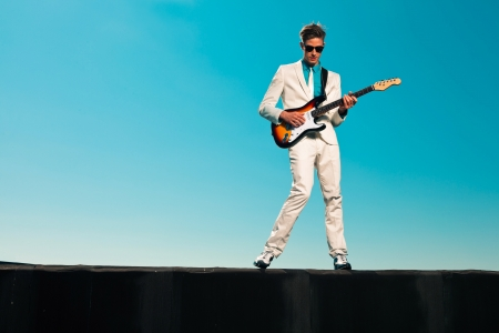 Vintage fifties male guitar player with white suit and sunglasses photo