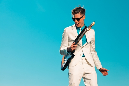 Retro fifties male electric guitar player wearing white suit and sunglasses Stock Photo