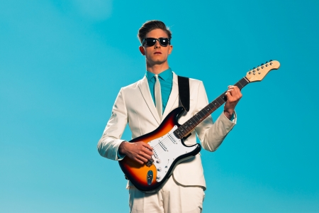 Retro fifties male electric guitar player wearing white suit and sunglasses photo