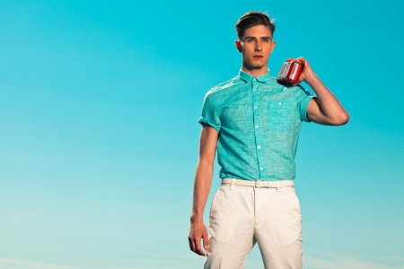 Retro fifties summer fashion man in blue shirt listens to portable radio photo