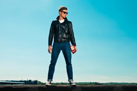 Rock and homem rolo estilo 50s com jaqueta preta. Segurando r Banco de Imagens