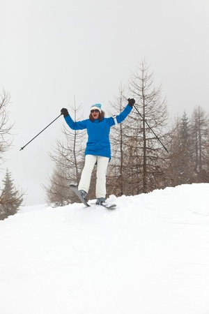 Happy ski woman standing in snow with pine trees. photo