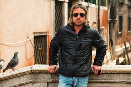 Young man with long blonde hair and sunglasses on bridge in Venice. Italy. photo