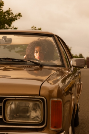 Retro 70s fashion african american woman driving in gold seventies car. Stock Photo