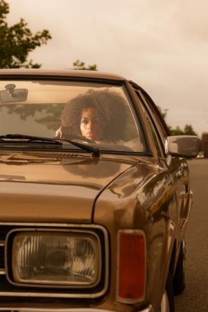 Retro 70s fashion african american woman driving in gold seventies car. Standard-Bild