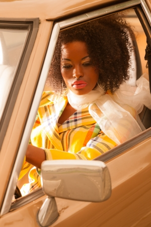 american sexy: Retro 70s fashion african american woman driving in gold seventies car. Stock Photo