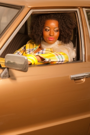 Retro 70s fashion african american woman driving in gold seventies car. photo