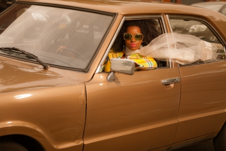 Vintage 70s fashion afro woman with sunglasses driving in brown seventies car. photo