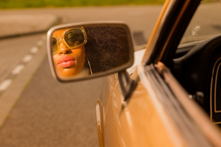 Retro 70s afro fashion woman with sunglasses looking in mirror of brown seventies car. photo