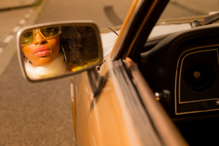sexy black girl: Retro 70s afro fashion woman with sunglasses looking in mirror of brown seventies car. Stock Photo