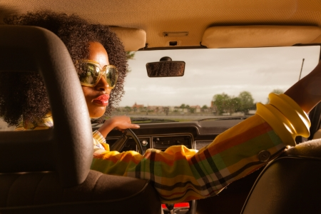 woman driving car: Retro 70s afro fashion woman with sunglasses driving in brown seventies car.