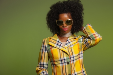 Dancing retro 70s fashion african woman with sunglasses. Yellow jacket and green background. photo