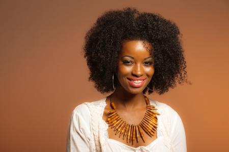 Vintage jaren '70 mode afro vrouw. Wit shirt en spijkerbroek tegen bruine achtergrond.