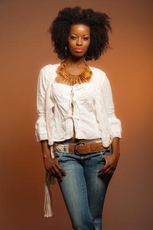 Vintage 70s moda mulher afro. Camisa branca e cal�a jeans contra um fundo marrom.