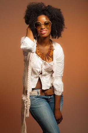 70 Vintage fashion mulher negra com �culos de sol. Camisa branca e jeans contra o fundo marrom.