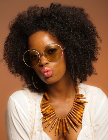 Retro 70s fashion black woman with sunglasses and white shirt. Brown background. photo
