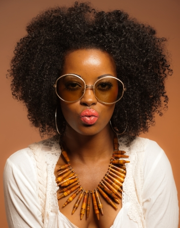 Retro 70s fashion black woman with sunglasses and white shirt. Brown background. Stock Photo