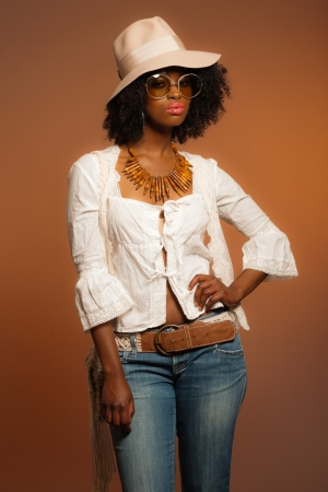 Retro 70s fashion afro woman with sunglasses and white hat. Brown background. Stock Photo - 20281249