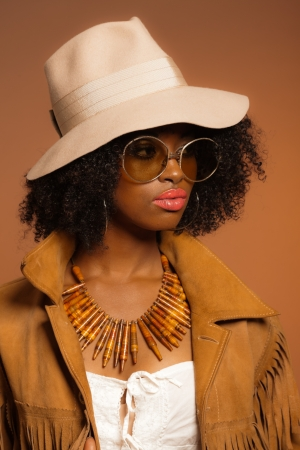 Retro 70s fashion afro woman with sunglasses and white hat. Brown background. photo