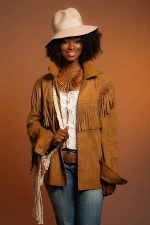 Retro 70s fashion african woman with white hat and brown jacket. Brown background. photo