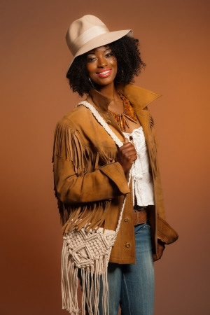 Retro 70s fashion african woman with white hat and brown jacket. Brown background.
