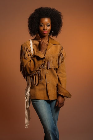 Vintage seventies fashion african woman with brown leather jacket. Brown background. photo
