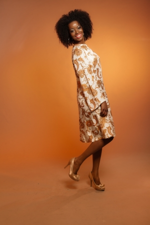 Happy retro seventies fashion african woman with paisley dress. Brown background. photo